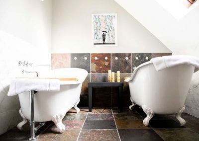 2 clawfoot tubs on each side of a long bathroom, with rustic bronze and copper colored tile on the floor.