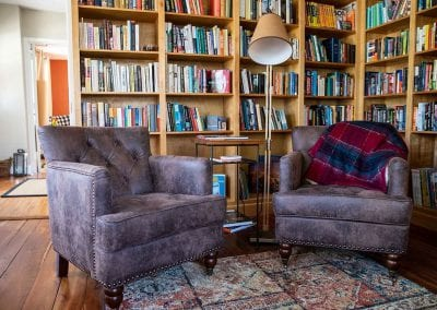 2 armchairs in front of bookshelves full of books