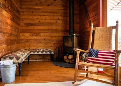 wood-paneled nook, wood-burning stove on the right, upholstered benches on the left, and a rocking chair.