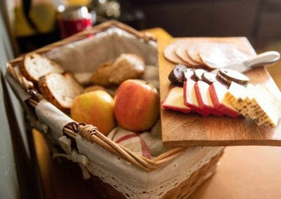 wooden tray with cheese and cold cuts above a wicker basket showing apples and bread