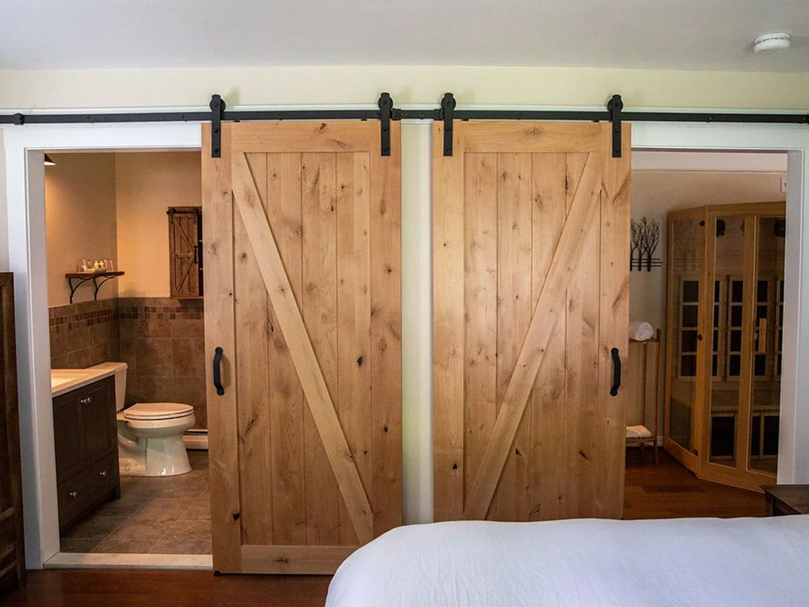 2 barn doors showing part of a bathroom on the left, part of an infrared sauna on the right, and part of a bed in the foreground
