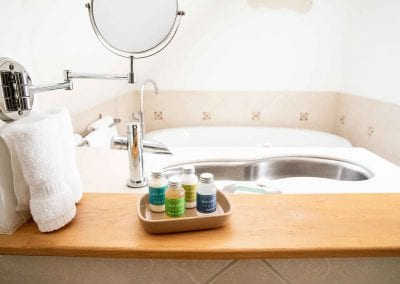 Bathroom amenities with view on sink and tub