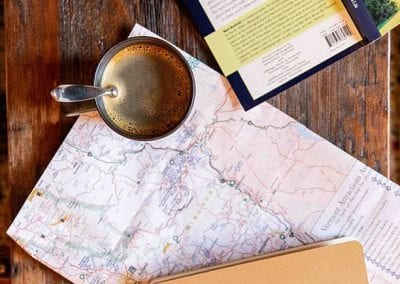 coffee cup on map near book and note book