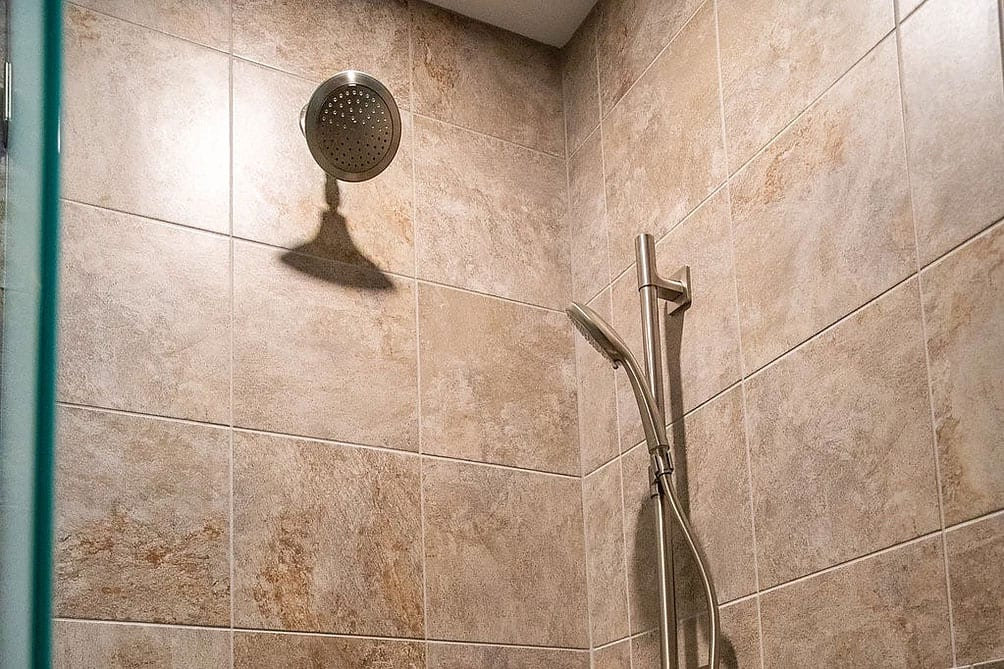 detail of a shower showing light brown, rustic tile and stainless steel handheld shower plus a rain shower head.