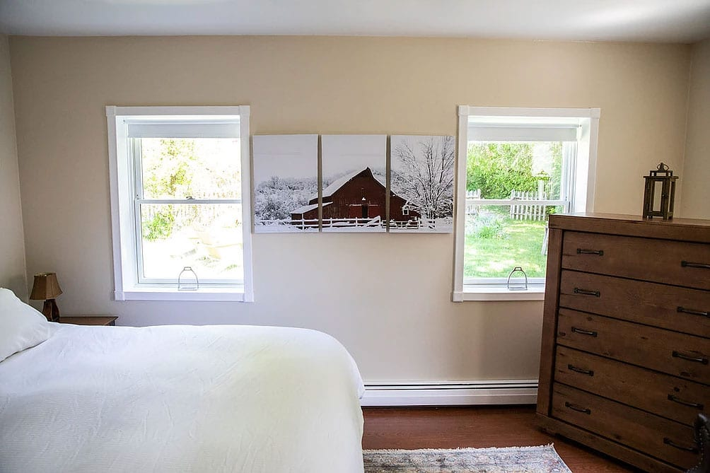 inside of a bedroom showing a triptych of a red barn in between 2 windows opening on a garden, part of the bed of the left and a chest of drawers with a lantern on the right.