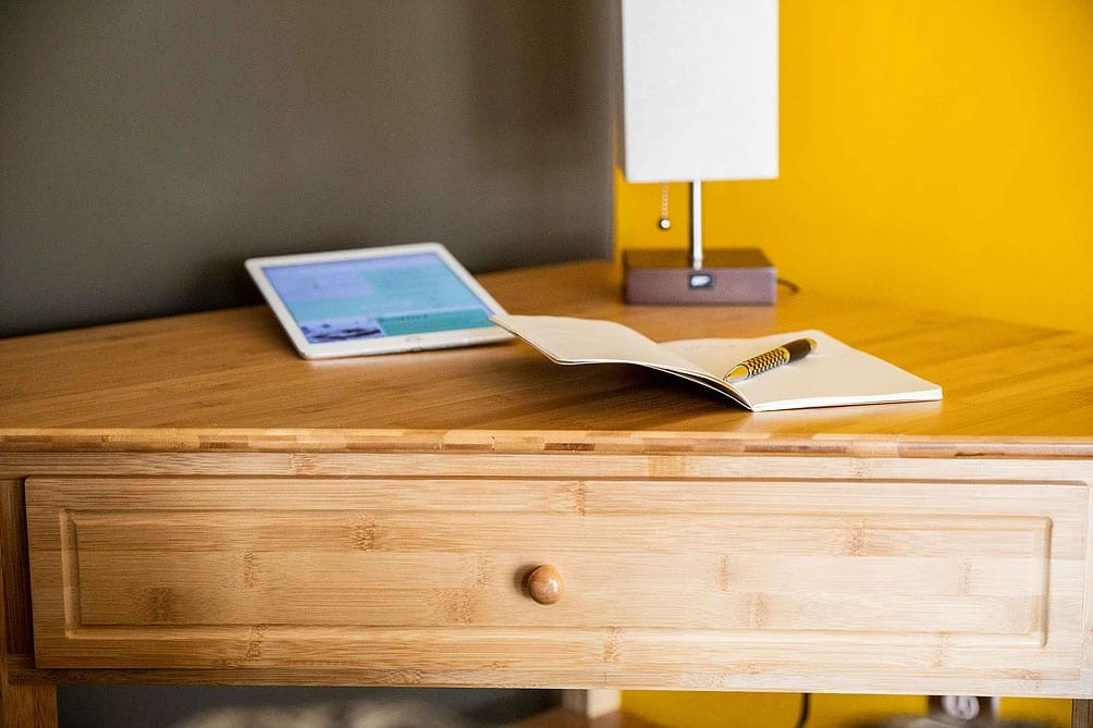 detail of a writing table showing the drawer in the foreground, a notepad and pen, tablet and lamp on the table.