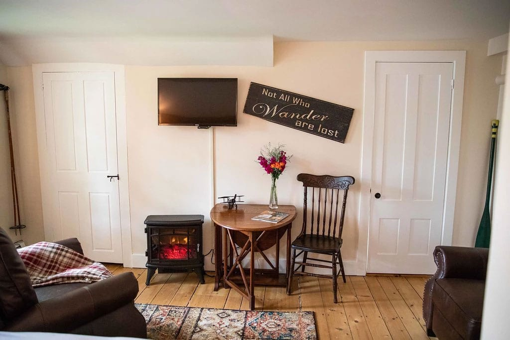 TV, infrared fireplace and table and chair with sign on wall