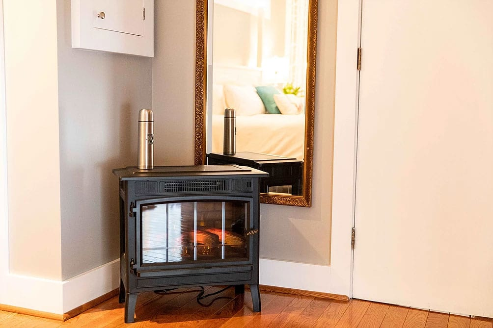 electric fireplace that looks like an old wood burning stove, and a long mirror behind framed in old gold color.