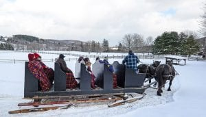 Large sleigh with passengers in a snowy landscape
