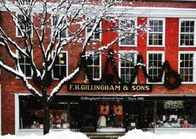 Red facade of a federal style building with many windows, the sign Gillingham's General Store, a snow-covered tree and sidewalks