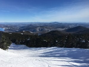 Breathtaking view from the summit of a mountain, with many mountains in the back and the beginning of a ski slope