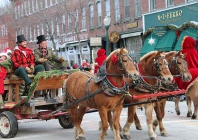 horse-drawn carriage decorated with greens and led by man in period costume