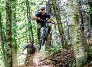 2 mountainbikers jump on their bikes in the woods