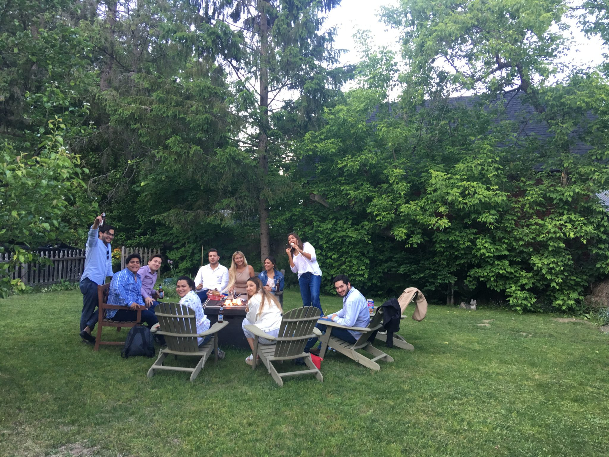 Several young couples sitting on Adirondack chairs, gathered around a firepit, smiling, some with beer in hand