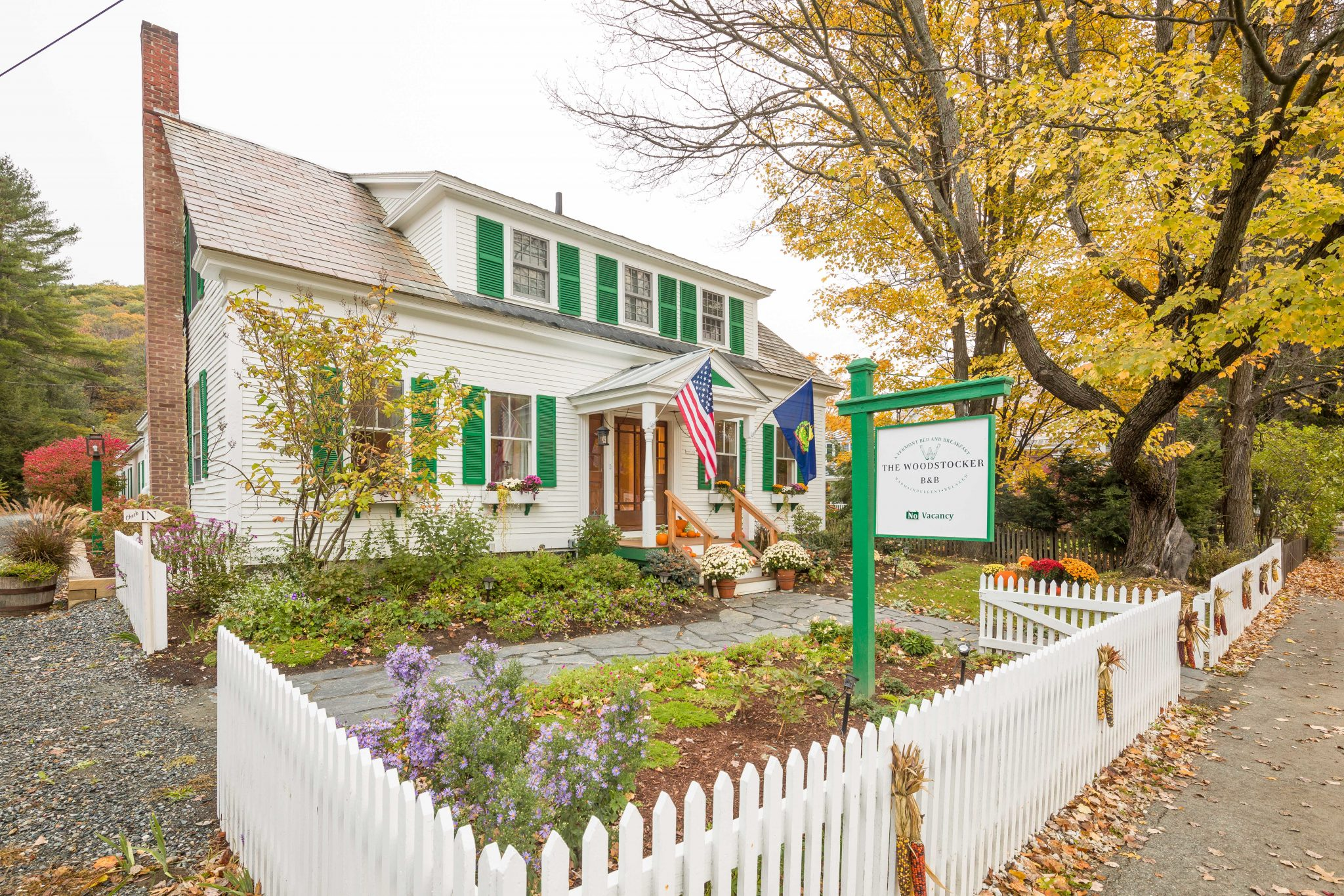 One story white house with green shutters, white picket fence and front garden in the fall
