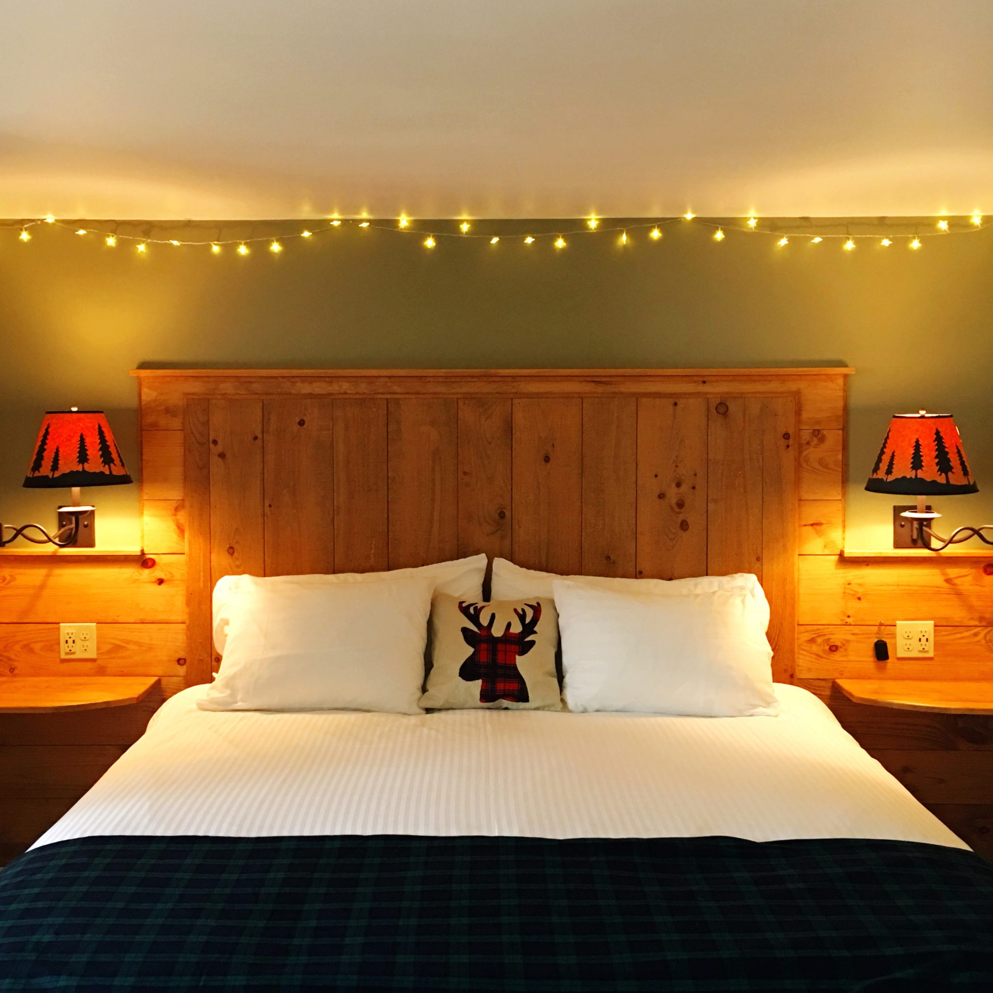 Wooden bed head with deer pillow and twinkling lights