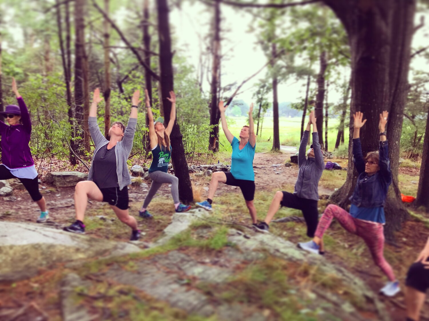 People in the woods in a yoga posture